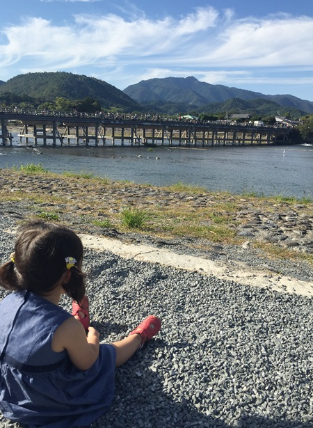嵐山渡月橋と川辺座って渡月橋見る