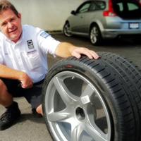 タイヤを抱える男性